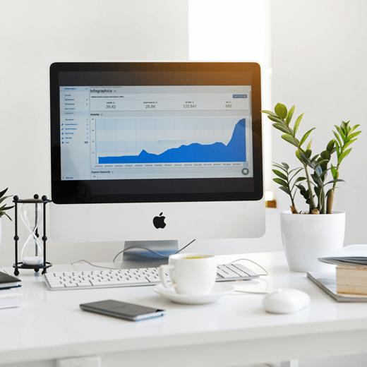 Desktop computer showcasing an increasing graph on a white modern desk